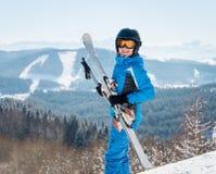 Gelukkige vrouwelijke skiër die aan de camera glimlachen, houdend haar skis, die blauw skikostuum en zwarte helm dragen bij de to stock afbeeldingen