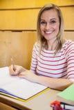 gelukkige vrouwelijke student het schrijven nota's stock afbeeldingen