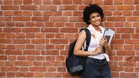 Gelukkige vrouwelijke student met boeken die zich bij muur bevinden Royalty-vrije Stock Fotografie