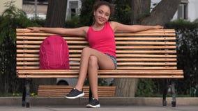 Gelukkige Vrouwelijke Student Relaxing And Resting op Parkbank stock video