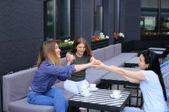 Gelukkige vrouwelijke vrienden die bij koffie zitten en handen houden Royalty-vrije Stock Afbeelding