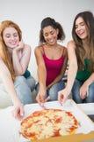Gelukkige vrouwelijke vrienden die pizza thuis eten Royalty-vrije Stock Afbeeldingen