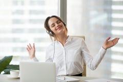 Gelukkige vrouwelijke werknemer die van favoriete muziek genieten op het werk stock afbeeldingen