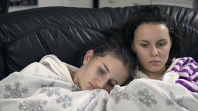 gelukkige vrouwelijke zusters die op TV op een bank thuis letten Royalty-vrije Stock Afbeelding