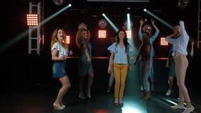 Gelukkige vrouwen die aan de muziek van partij met binnen haar dansen andere meisjesvrienden op de dansvloer van een modieuze nac stock footage