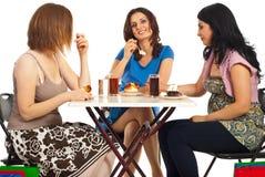 Gelukkige vrouwen die cakes eten bij lijst Stock Foto's