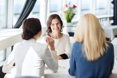 Gelukkige vrouwen die en bij restaurant samenkomen spreken stock foto