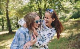 Gelukkige vrouwen die en over aardachtergrond omhelzen lachen stock foto's
