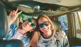 Gelukkige vrouwen die en pret binnen van auto hebben lachen royalty-vrije stock fotografie