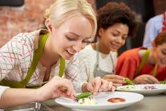 Gelukkige vrouwen die en schotels koken verfraaien Stock Foto's