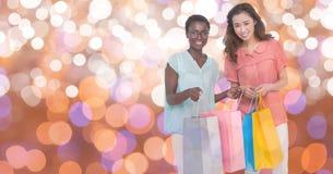 Gelukkige vrouwen die het winkelen zakken over bokeh dragen stock afbeeldingen