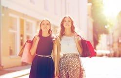 Gelukkige vrouwen die met het winkelen zakken in stad lopen Royalty-vrije Stock Foto's