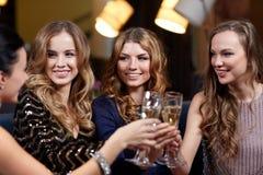 Gelukkige vrouwen met champagneglazen bij nachtclub Stock Fotografie