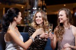 Gelukkige vrouwen met champagneglazen bij nachtclub Stock Foto's