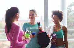 Gelukkige vrouwen met flessen water in gymnastiek royalty-vrije stock afbeeldingen
