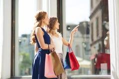 Gelukkige vrouwen met het winkelen zakken bij winkelvenster Stock Afbeeldingen