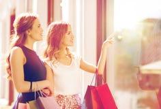 Gelukkige vrouwen met het winkelen zakken bij winkelvenster Stock Foto's