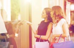 Gelukkige vrouwen met het winkelen zakken bij winkelvenster Stock Fotografie