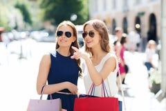 Gelukkige vrouwen met het winkelen zakken in stad Royalty-vrije Stock Fotografie