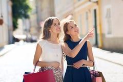 Gelukkige vrouwen met het winkelen zakken in stad Stock Afbeeldingen