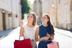 Gelukkige vrouwen met het winkelen zakken in stad Royalty-vrije Stock Foto