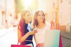 Gelukkige vrouwen met het winkelen zakken in stad Stock Foto