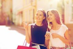 Gelukkige vrouwen met het winkelen zakken in stad Stock Afbeelding