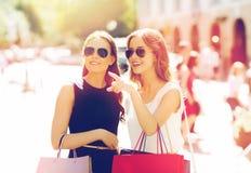 Gelukkige vrouwen met het winkelen zakken in stad Stock Foto's