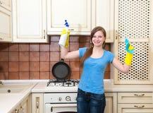 Gelukkige vrouwen schoonmakende keuken Mooi meisje met het schoonmaken van nevel stock afbeelding