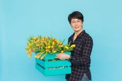 Gelukkige vrouwenbloemist die op middelbare leeftijd glazen met doos van tulpen op blauwe achtergrond dragen stock afbeeldingen