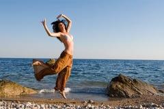 Gelukkige vrouwendans in het strand Royalty-vrije Stock Afbeeldingen