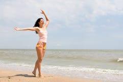 Gelukkige vrouwendans op het strand Stock Foto