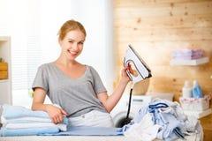 Gelukkige vrouwenhuisvrouw het strijken kleren in wasserij thuis stock afbeelding