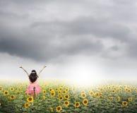 Gelukkige vrouwensprong op zonnebloemgebieden en rainclouds Stock Afbeeldingen
