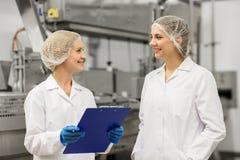 Gelukkige vrouwentechnologen bij roomijsfabriek Stock Foto's