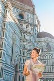 Gelukkige vrouwentoerist die met kaart op iets dichtbij Duomo kijken stock fotografie