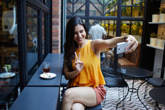 Gelukkige vrouwentoerist die zelfportret met slimme telefooncamera maken terwijl het zitten in het moderne binnenland van de koff Royalty-vrije Stock Afbeelding