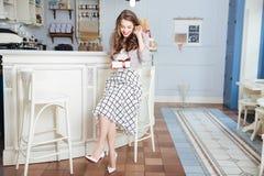 Gelukkige vrouwenzitting in koffie en holdingsgift Royalty-vrije Stock Foto