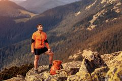 Gelukkige wandelaar die bereikend het levensdoel, succes, vrijheid en geluk, voltooiing in bergen winnen royalty-vrije stock afbeelding