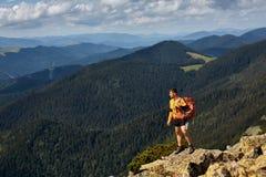 Gelukkige wandelaar die bereikend het levensdoel, succes, vrijheid en geluk, voltooiing in bergen winnen royalty-vrije stock foto