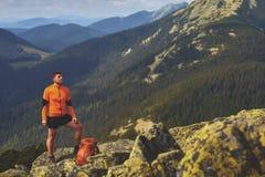 Gelukkige wandelaar die bereikend het levensdoel, succes, vrijheid en geluk, voltooiing in bergen winnen royalty-vrije stock fotografie