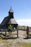 Gelukkige wandelaars die dichtbij kleine bergkerk in bergaard op zonnige dag rusten Royalty-vrije Stock Foto