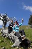 Gelukkige wandelaars die en hello op oude boomboomstam rusten golven in bergaard op zonnige dag Royalty-vrije Stock Foto