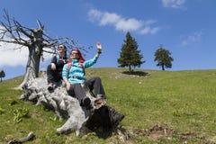 Gelukkige wandelaars die en hello op oude boomboomstam rusten golven in bergaard op zonnige dag Stock Foto's
