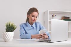 Gelukkige weggegaane mooie vrouw die op kantoor werken Jonge mooie vrouw die telefoon met behulp van stock fotografie