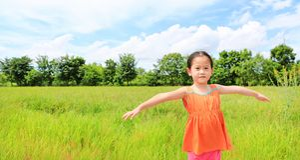 Gelukkige weinig Aziatische rekwapens van het jong geitjemeisje en ontspannen bij de jonge groene padiegebieden stock fotografie