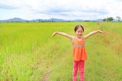 Gelukkige weinig Aziatische rekwapens van het jong geitjemeisje en ontspannen bij de jonge groene padiegebieden met berg en wolke royalty-vrije stock foto
