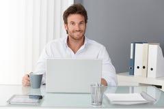 Gelukkige zakenman in bureau Stock Foto's