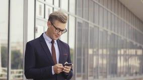 Gelukkige zakenman die aangezien hij een tekstbericht glimlachen leest die zich buiten het bureau bevinden Mannelijke uitvoerende stock video