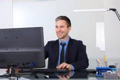 Gelukkige zakenman die computer in zijn bureau met behulp van Royalty-vrije Stock Foto